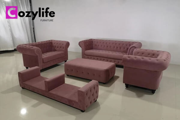 pink fabric chesterfield sofa with tables